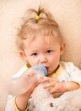Child girl with bottle with infant formula at home Royalty Free Stock Photography