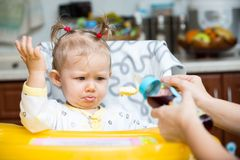 Child girl with bottle with infant formula on kitchen. Royalty Free Stock Photo