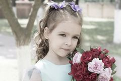 Child girl with bouquet of roses. Tender portrait royalty free stock images