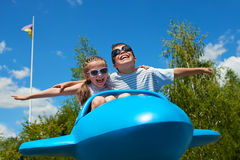 Child girl and boy fly on blue plane attraction in city park, happy childhood, summer vacation concept Royalty Free Stock Image
