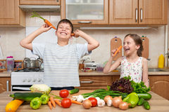 Child girl and boy having fun with tomatoes and carrot. Home kit Royalty Free Stock Photography