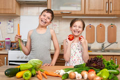 Child girl and boy having fun with tomatoes and carrot. Home kitchen interior with fruits and vegetables. Healthy food concept Stock Photos