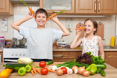 Child girl and boy having fun with tomatoes and carrot. Home kitchen interior with fruits and vegetables. Healthy food concept Stock Images