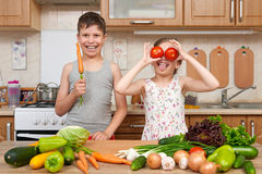 Child girl and boy having fun with tomatoes and carrot, look through like binoculars. Home kitchen interior with fruits and vegeta Stock Image