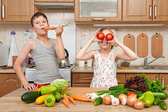 Child girl and boy having fun with tomatoes and carrot, look through like binoculars. Home kitchen interior with fruits and vegeta Royalty Free Stock Photos
