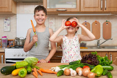 Child girl and boy having fun with tomatoes and carrot, look through like binoculars. Home kitchen interior with fruits and vegeta Stock Photos