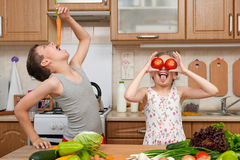 Child girl and boy having fun with tomatoes and carrot, look through like binoculars. Home kitchen interior with fruits and vegeta Royalty Free Stock Photo