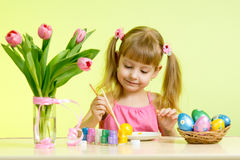 Child girl with brush coloring easter eggs. Kid girl with brush coloring easter eggs royalty free stock images