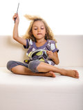 Child girl brushing hair on sofa Royalty Free Stock Images