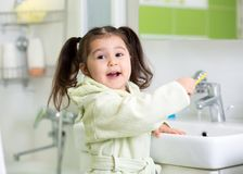 Child girl brushing teeth in bathroom Royalty Free Stock Images