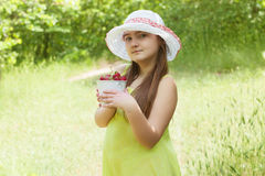 Child girl with bucket of strawberries Royalty Free Stock Images