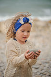 Child girl building stone tower on the beach. Cute curly child girl building stone tower on the beach in summer day Stock Images