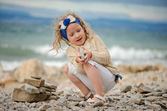 Child girl building stone tower on the beach. Cute curly child girl building stone tower on the beach in summer day Royalty Free Stock Photography