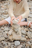 Child girl building stone tower on the beach. In summer day Stock Images
