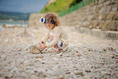 Child girl building stone tower on the beach in summer day Royalty Free Stock Photography