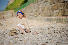 Child girl building stone tower on the beach in summer day Stock Photos