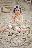 Child girl building stone tower on the beach in summer day Royalty Free Stock Images