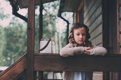 Child girl with candle holder relaxing in evening at cozy country house. Stock Photography