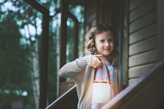 Child girl with candle holder relaxing in evening at cozy country house. Royalty Free Stock Image