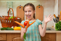 Child girl with carrot and tomatoes, vegetables and fresh fruits in kitchen interior, healthy food concept Stock Images