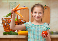 Child girl with carrot and tomatoes, vegetables and fresh fruits in kitchen interior, healthy food concept Royalty Free Stock Image