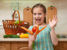 Child girl with carrot and tomatoes, vegetables and fresh fruits in kitchen interior, healthy food concept Stock Photo