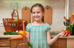Child girl with carrot and tomatoes, vegetables and fresh fruits in kitchen interior, healthy food concept Royalty Free Stock Photos