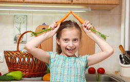 Child girl with carrot, vegetables and fresh fruits in kitchen interior, healthy food concept Stock Photo
