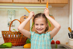 Child girl with carrot, vegetables and fresh fruits in kitchen interior, healthy food concept Stock Photography