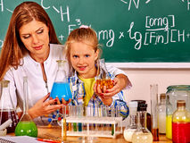 Child girl and chemistry teacher holding flask in chemistry class. Royalty Free Stock Photo