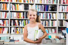 Child girl chose a lot of books in the library. Beautiful child girl chose a lot of books in the library Royalty Free Stock Image