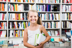Child girl chose a lot of books in the library. Happy child girl chose a lot of books in the library Royalty Free Stock Photo