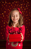 Child girl with christmas present on dark red with lights Stock Photo