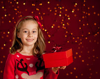 Child girl with christmas present on dark red with lights Royalty Free Stock Photo