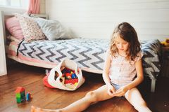 Child girl cleaning her room and organise wooden toys into knitted storage bag. Housework and help concept Royalty Free Stock Photo