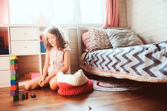 Child girl cleaning her room and organize wooden toys into knitted storage bag. Housework and help concept Royalty Free Stock Photo