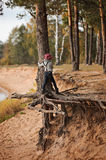 Child girl climbing old pine tree on the walk on river side Royalty Free Stock Photo