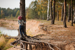 Child girl climbing old pine tree on the walk on river side. Child girl climbing old pine tree with huge roots on the walk on river side Royalty Free Stock Photography