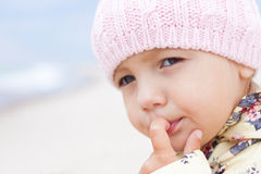 Child girl close-up outdoor. Child girl looking thinking with finger at mouth Stock Image