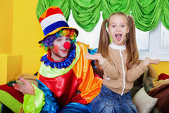 Child girl and clown playing on birthday party. Smiling child girl and clown with colourful cap playing on birthday party. Clown in rainbow colors costume Royalty Free Stock Photo