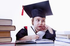 Child girl college graduate thinking about future perspectiv. Humorous photo. Knowledge, studies, work, career concept.  stock photography