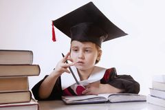 Child girl college graduate thinking about her perspectiv and future job. Humorous photo. (Knowledge, studies, work, career. Child girl college graduate thinking royalty free stock image