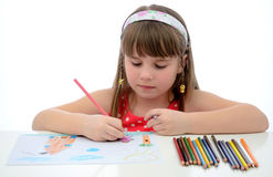 Child girl with colored crayons. Young girl making a new draw with colored crayons Stock Images