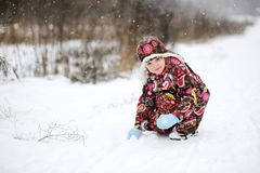 Child girl in colorful snowsiut plays in snow Royalty Free Stock Photos