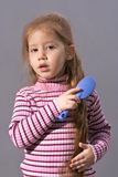 Child girl with comb brushing. Redheaded elementary age girl grooming her long hair using blue brush Stock Photography