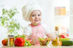 Child girl in cook hat eating vegetables Stock Photos