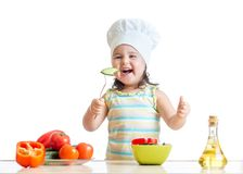 Child girl in cook hat eating vegetables Stock Photography