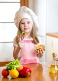 Child girl in cook hat eating vegetables Royalty Free Stock Image