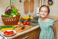 Child girl cooking in home kitchen. Basket of vegetables and fresh fruits in kitchen interior. Healthy food concept Stock Photos