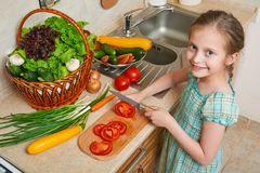 Child girl cooking in home kitchen, chopping tomatoes. Basket of vegetables and fresh fruits in kitchen interior. Healthy food con Royalty Free Stock Photo